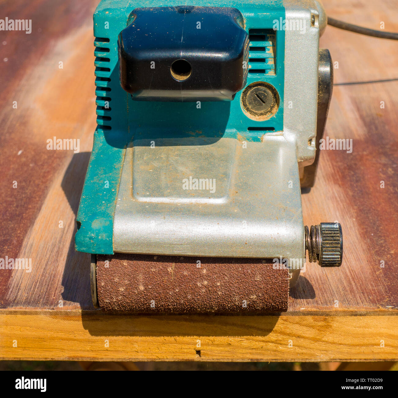 Heavy duty belt sander power tool, fitted with a coarse sanding belt, being used on an internal door, to remove the old varnish from the wood surface. - Stock Image