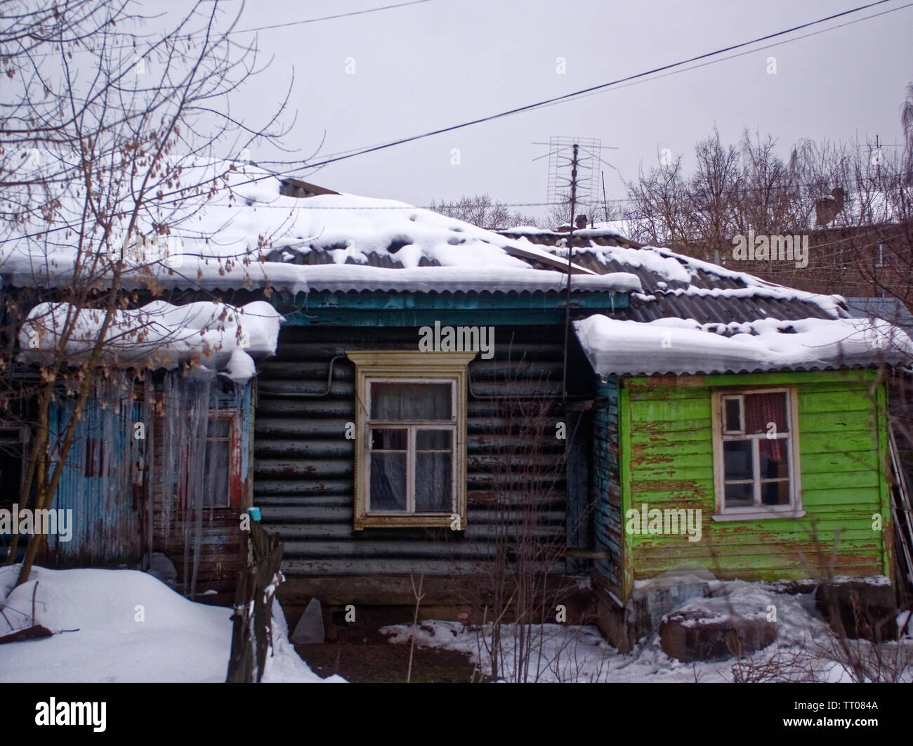 large icicles hanging from the roof of a wooden house, Russia - Stock Image