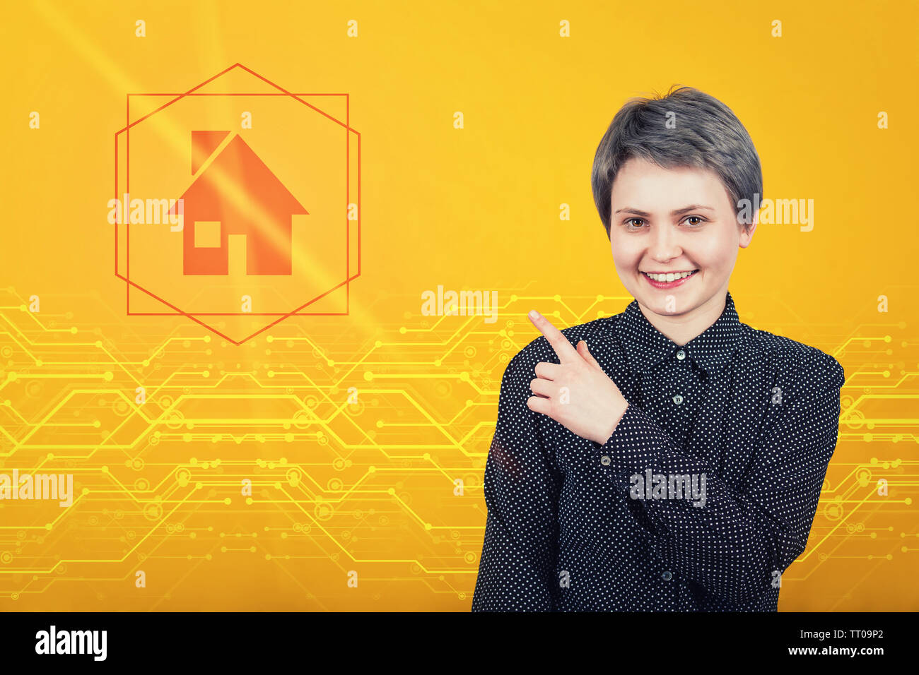 Beautiful young woman pointing forefinger away, showing to digital house on icon. Modern technology, property insurance concept. Home symbol. - Stock Image