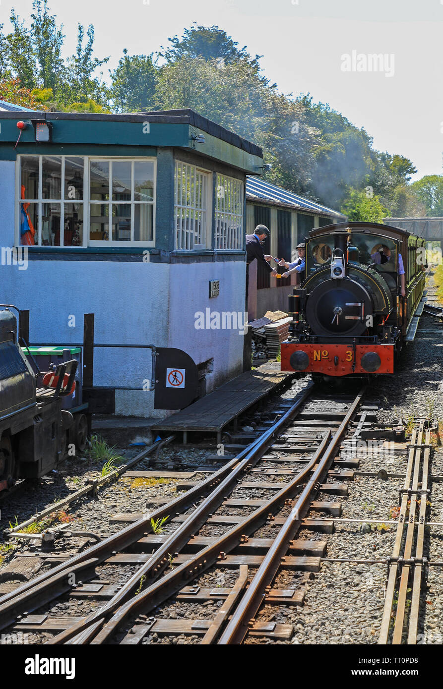 The driver of Steam engine number 3, 'Sir Haydn' exchanging or passing a token to the signalman on the Talyllyn Railway, Gwynedd, Wales, UK - Stock Image