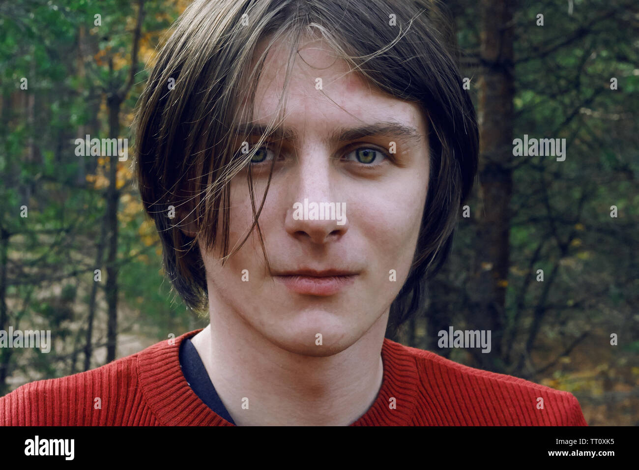 A handsome guy with long tousled hair and green eyes stands in the middle of the autumn forest - Stock Image