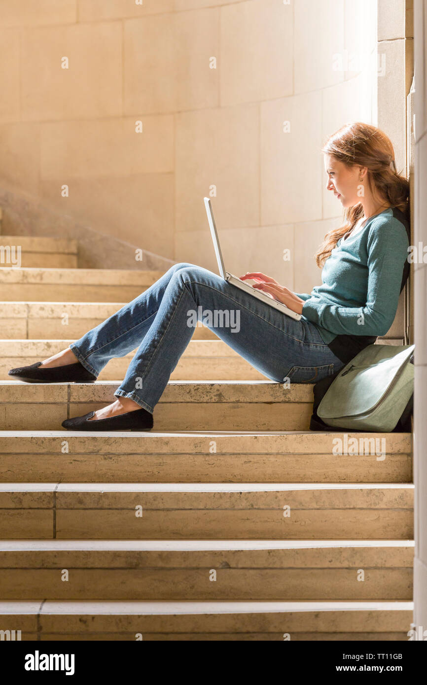 Young woman female college university student with laptop computer studying on campus - Stock Image