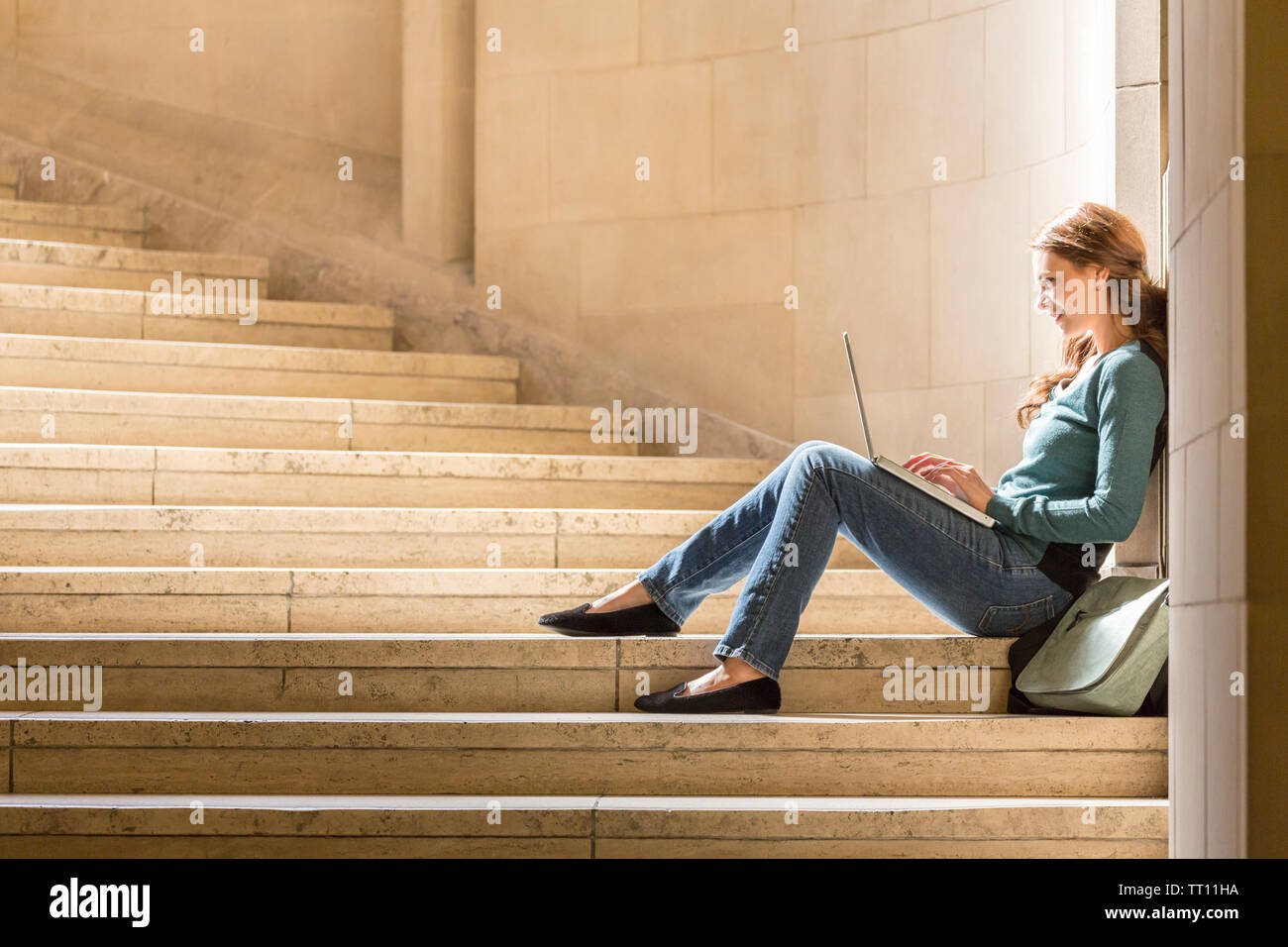 Happy, smiling young woman female college university student with laptop computer studying on campus - Stock Image