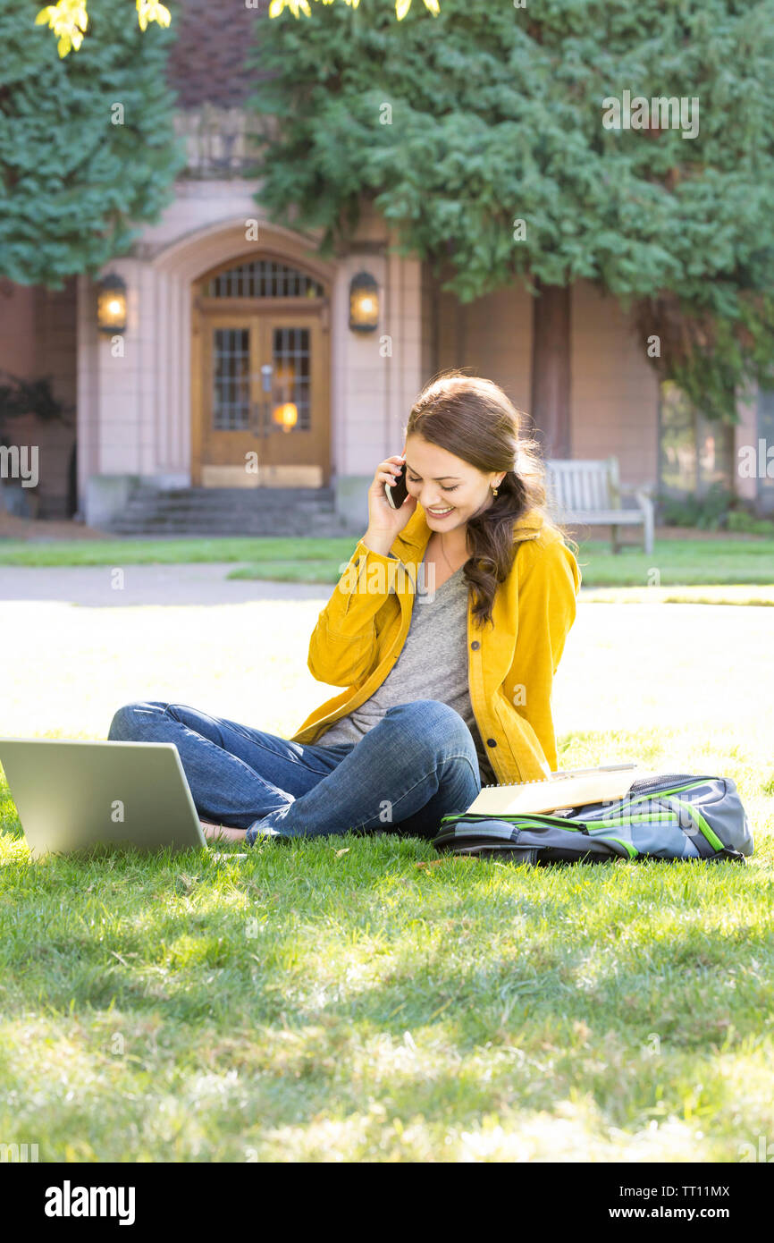 Happy, smiling, young woman female college university student  with laptop computer talking on cell phone outdoors on campus - Stock Image