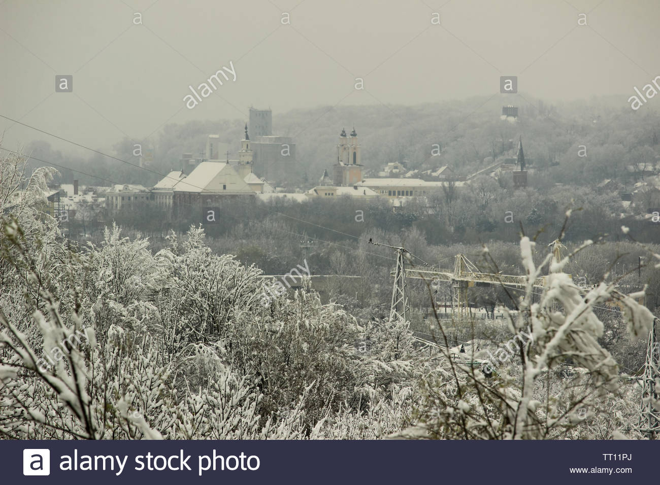 Moody Winter Landscape With the Snowy Frost Trees on a Hill, an Old Town's Buildings in a Hollow in Front of a Foggy Hill in a Horizon - Stock Image