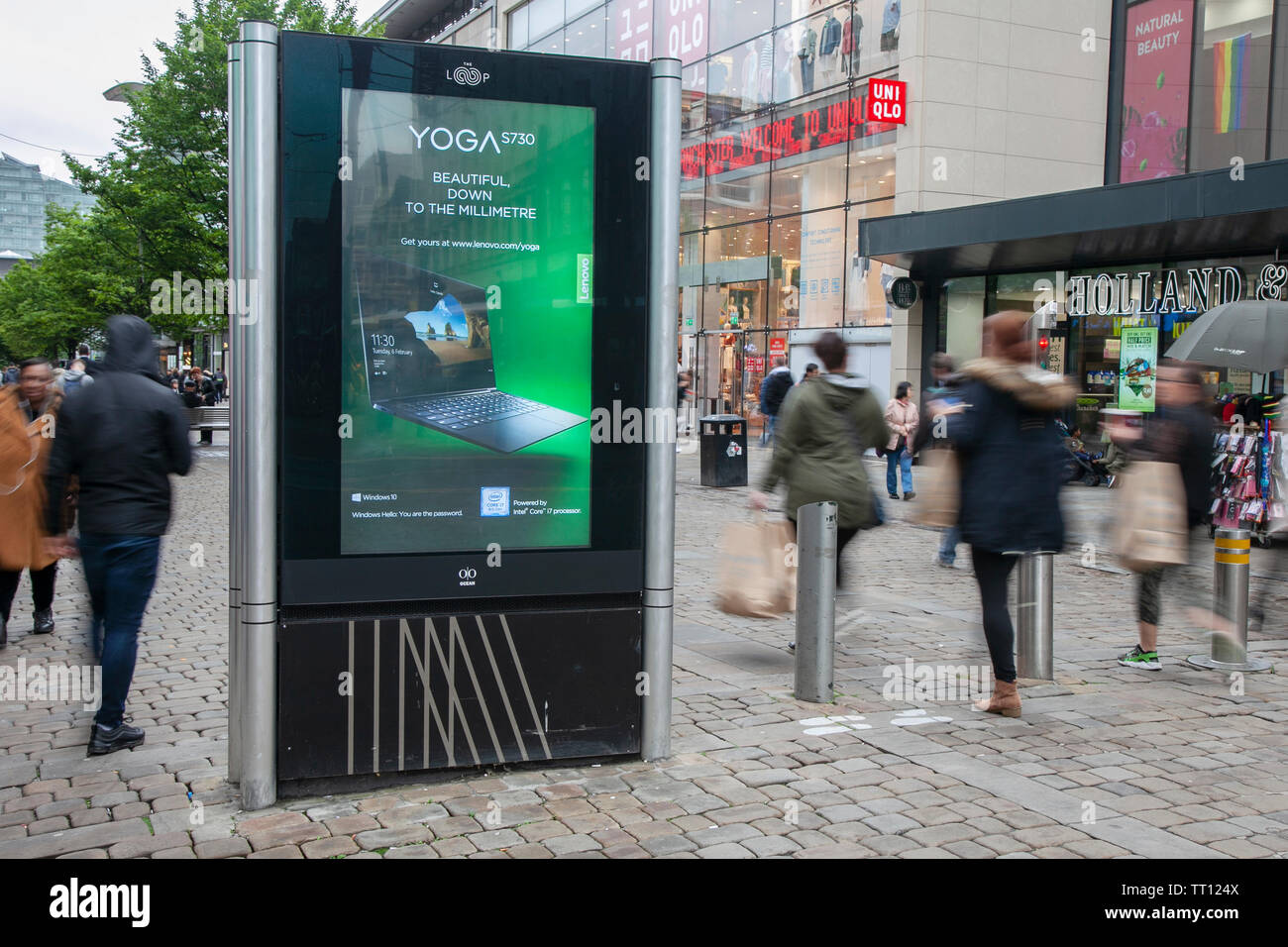 People passing Advertising sign for  Yoga S730 Shops, shoppers, retail business district, Piccadilly, Manchester city centre, UK - Stock Image