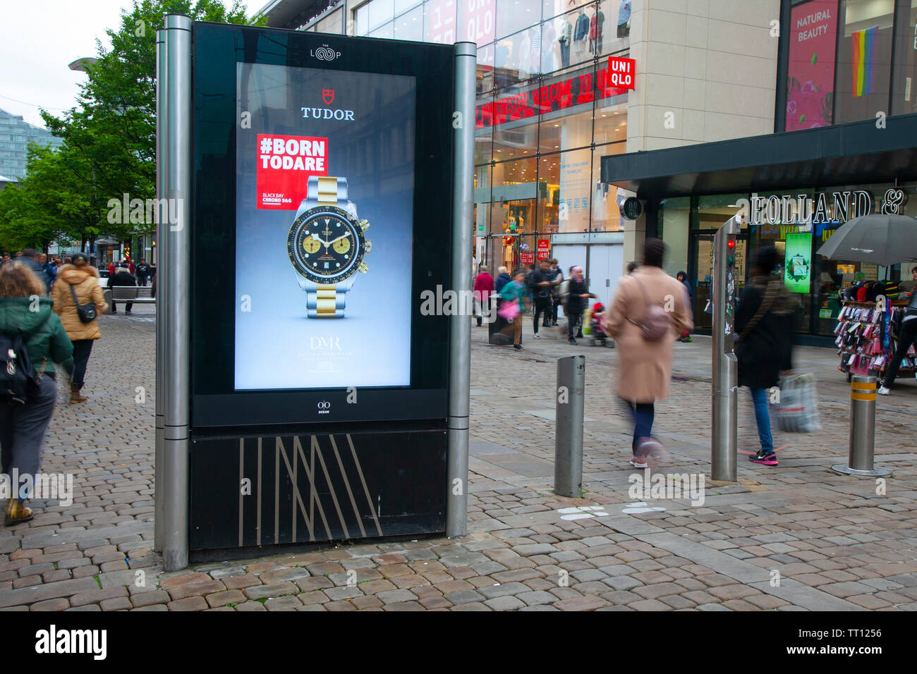 People passing Tudor watch advertising sign; Shops, shoppers, retail business district, Piccadilly, Manchester city centre, UK - Stock Image