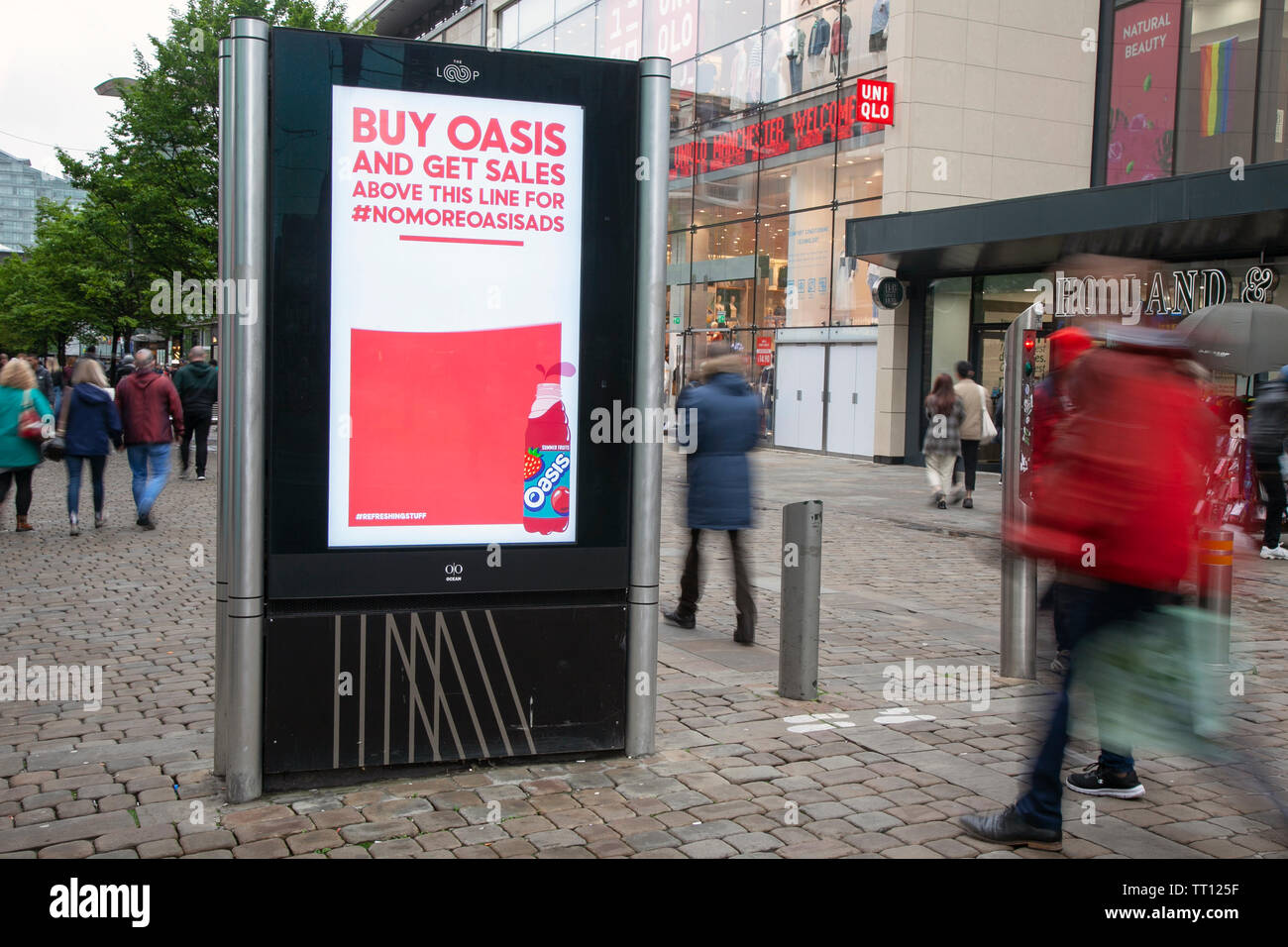 People passing Stop advertising Oasis ads, Shops, shoppers, retail business district, Manchester city centre, UK - Stock Image