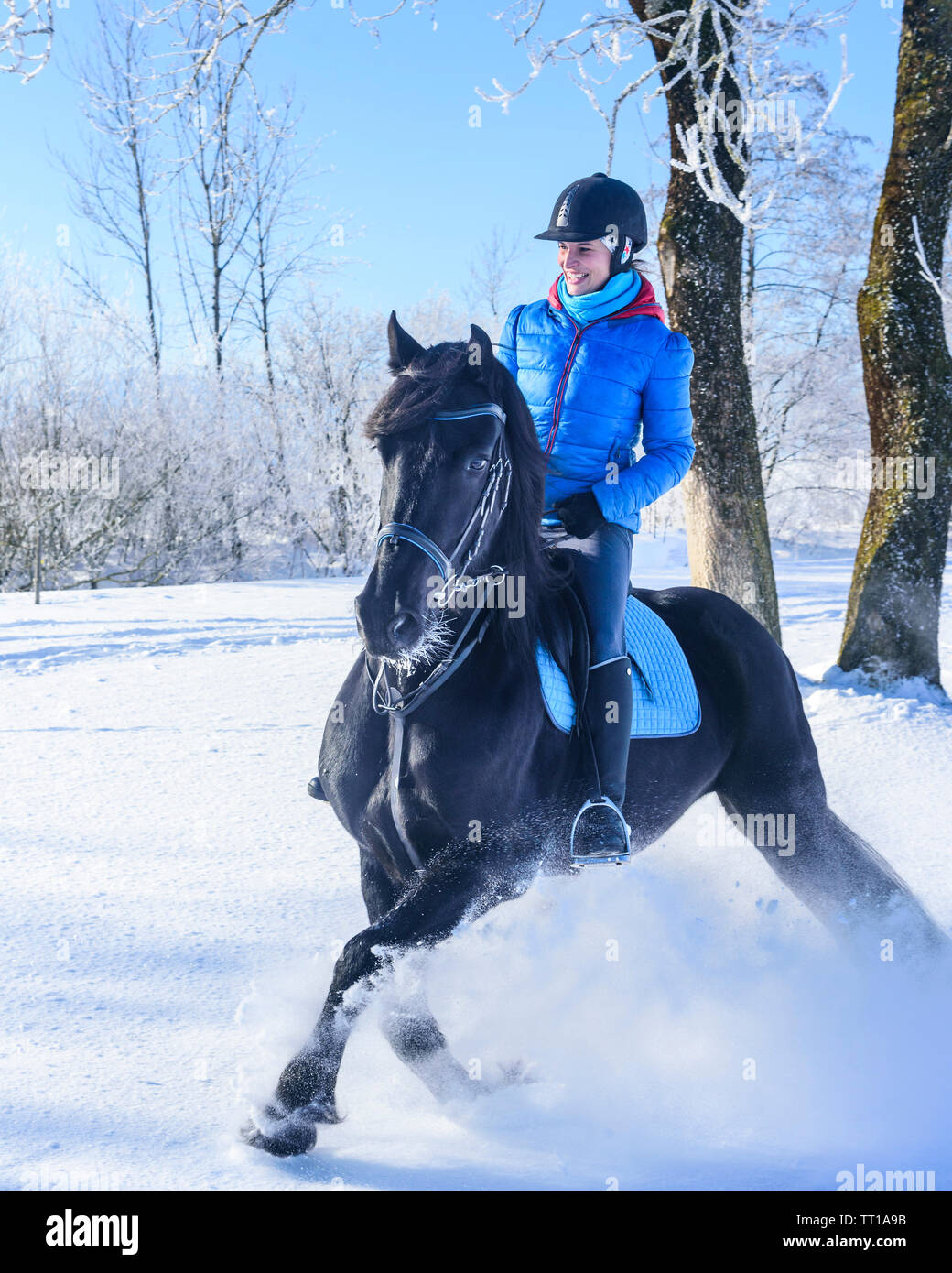 Sporty female rider doing a ride into the snowy nature in Allgäu - Stock Image