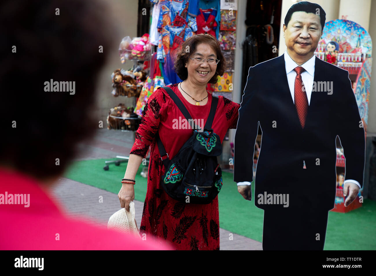 Chinese tourists photographed against the portrait of Chinese leader XI Jinping on Arbat street in the center of Moscow, Russia - Stock Image