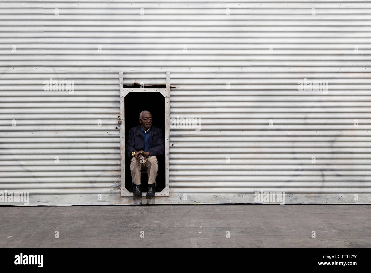 The Cuban man Raul Portillo Sama sits in a door frame in a corrugated sheet metal wall, behind which are stacks of eggs waiting to be sold. The performance installation is the work of Kosovar Albanian artist Sislej Xhafa, and is prominently on display at the 49th annual Art Basel Art Fair in Basel. - Stock Image