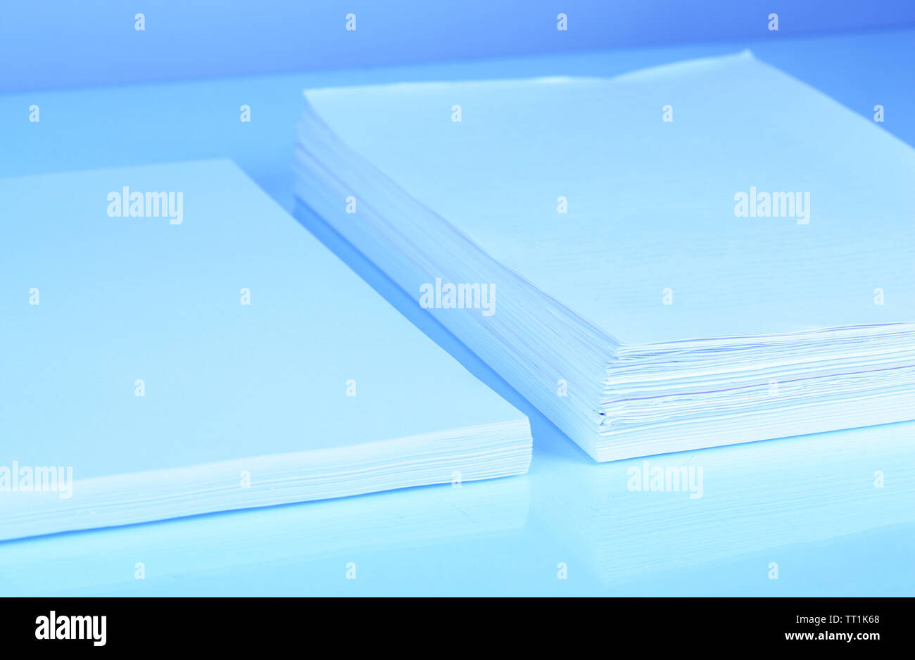 Stacks white paper in blue light - Stock Image
