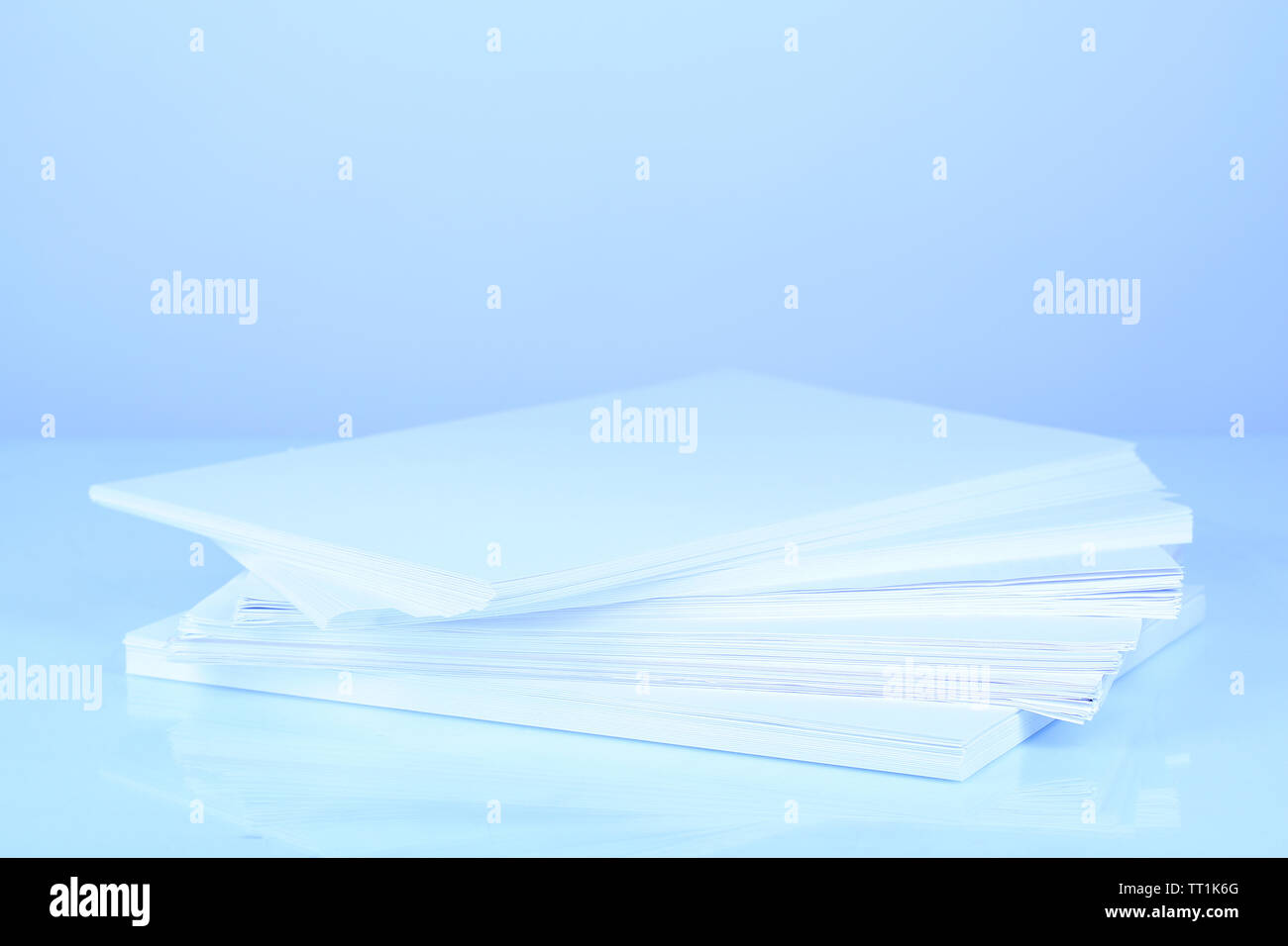 Stack white paper in blue light - Stock Image