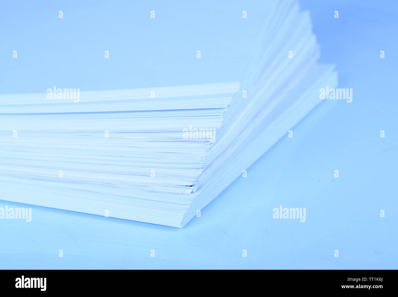 Stack white paper close-up in blue light - Stock Image