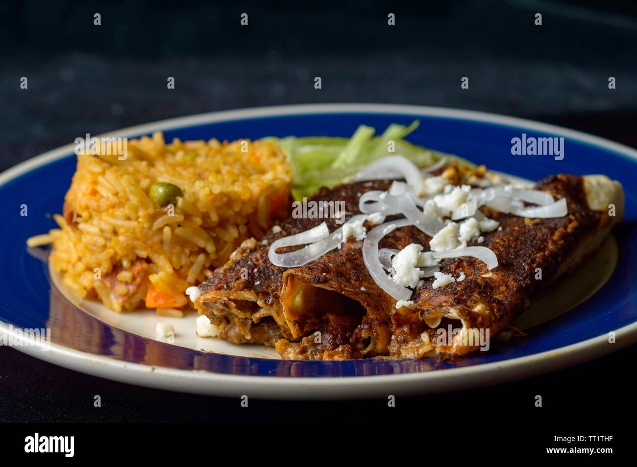 Mexican enmoladas, enchiladas topped with mole sauce and queso fresco, served with rice and salad. Isolated on dark background with copy space Stock Photo
