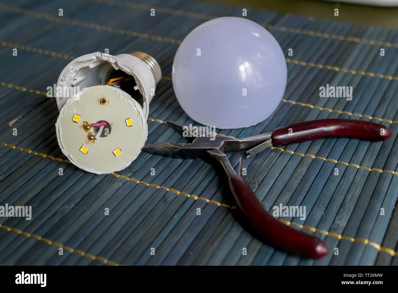 disassembled led household lamp with a burnt led element is on the table next to the pliers - Stock Image