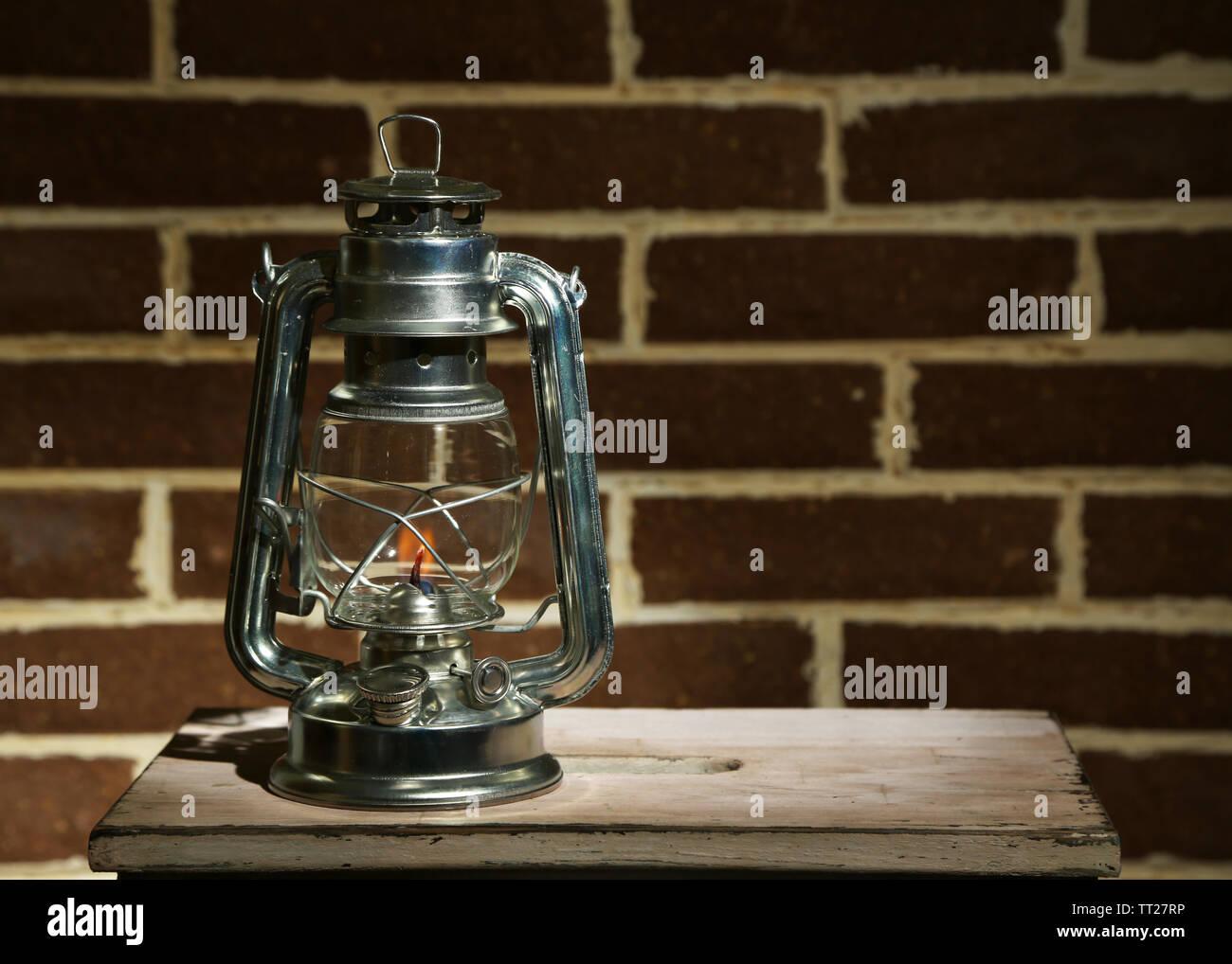 Burning kerosene lamp on brick wall background - Stock Image