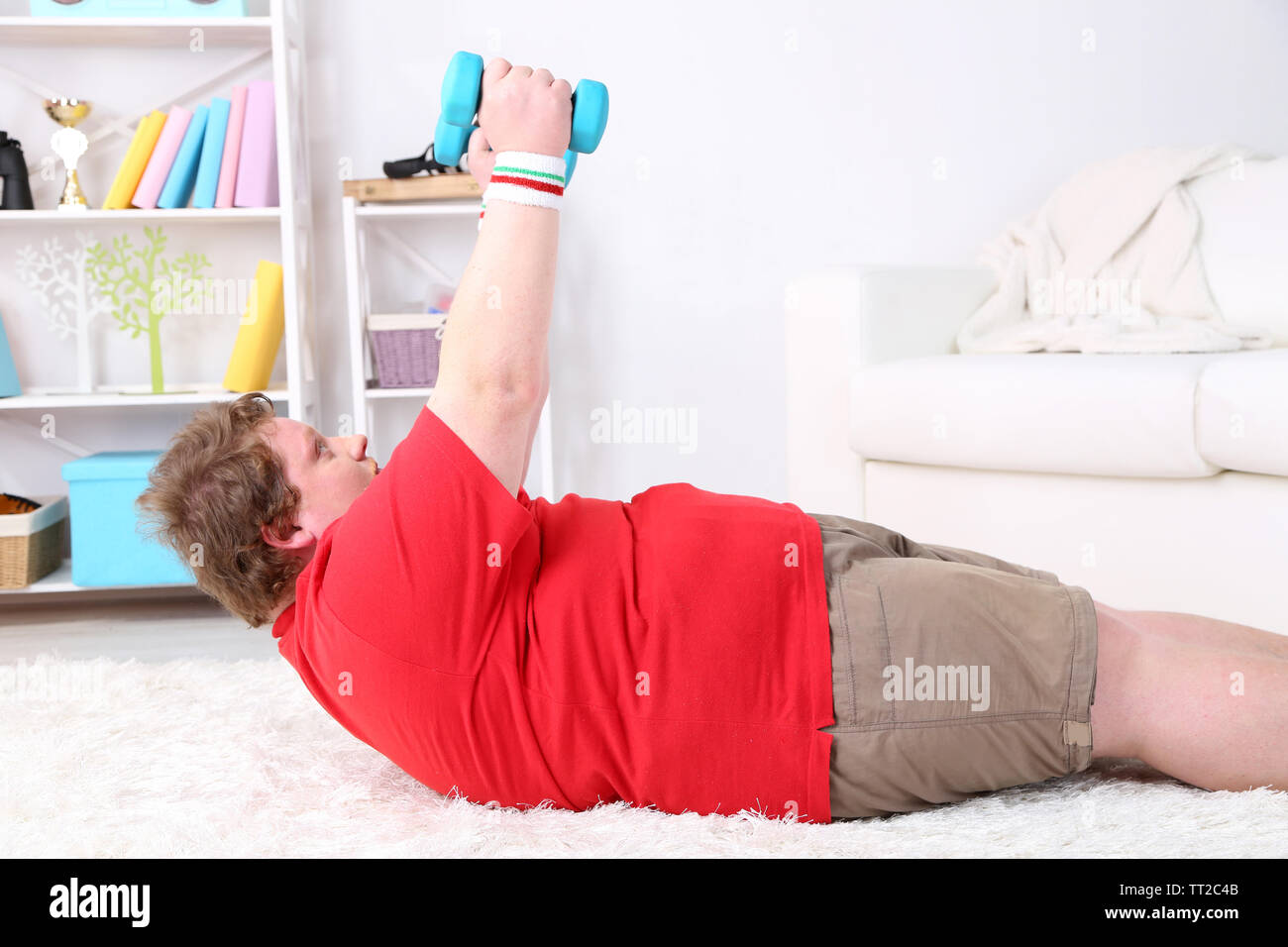Large fitness man making exercises with dumbbells on floor