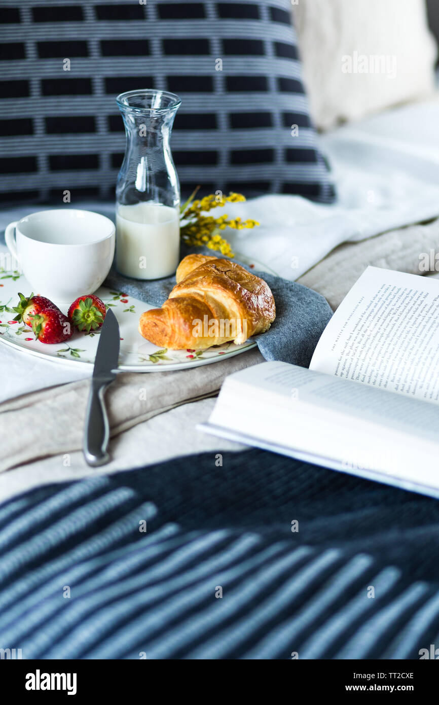 Breakfast of croissant, strawberries and coffee served in bed with an open novel - Stock Image