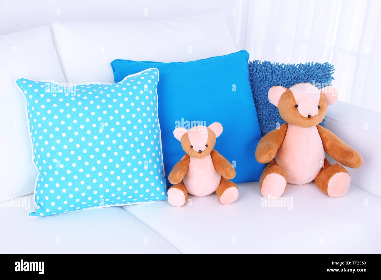 Two bears toy with pillows on sofa - Stock Image