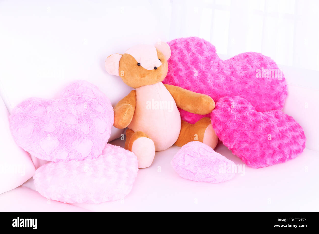 Bear toy with pillows on sofa - Stock Image