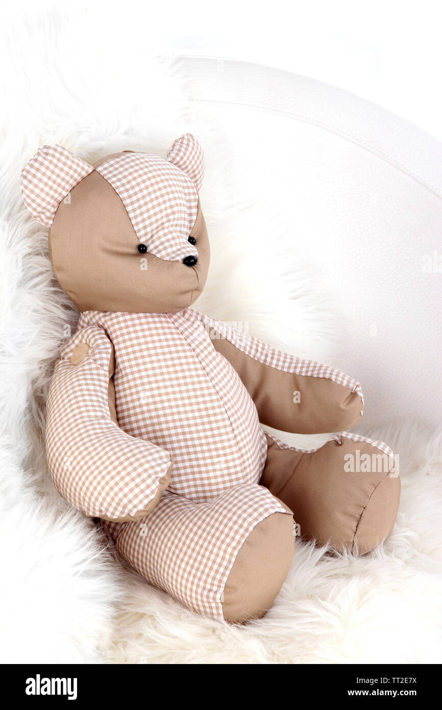 Bear toy on armchair in room - Stock Image