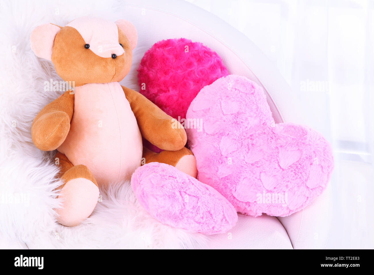 Bear toy with pillows on armchair in room - Stock Image