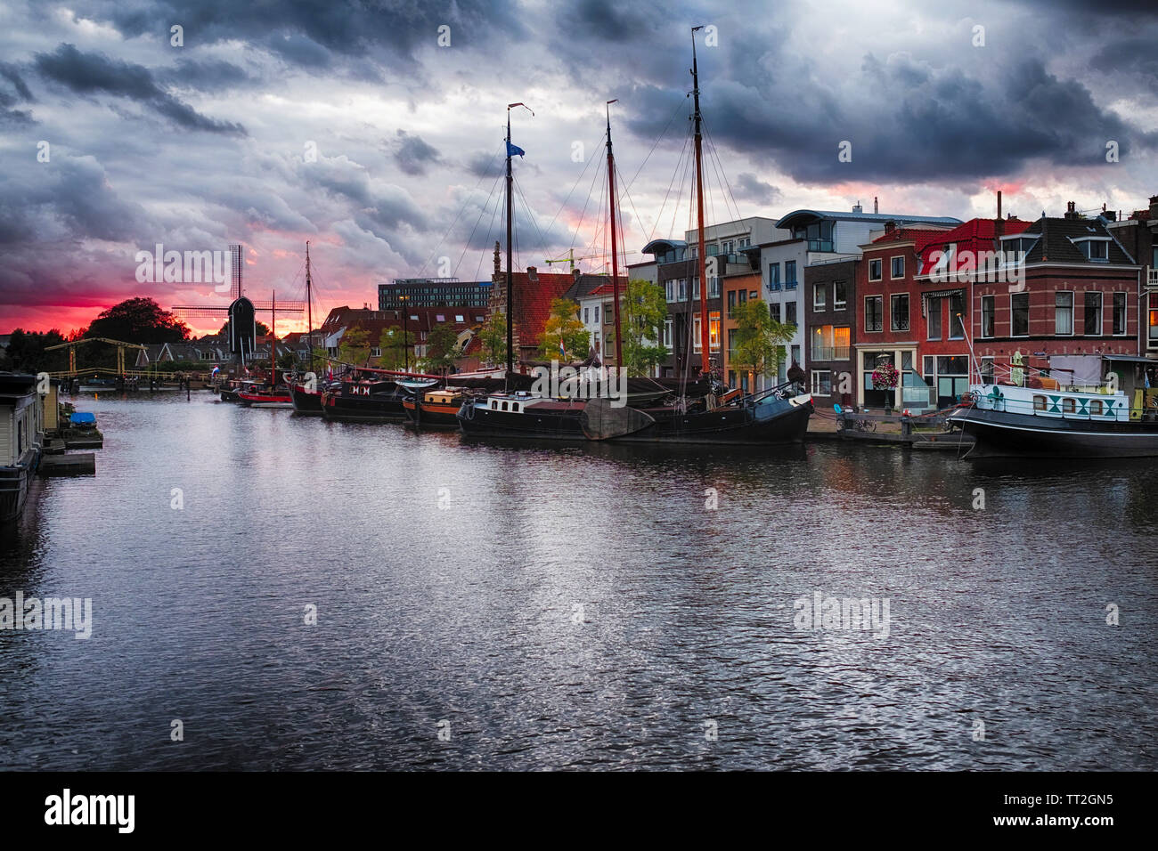 Canal woth Old Ships a Windmill and a Drawbridge at Sunset, Leiden, Netherlands Stock Photo
