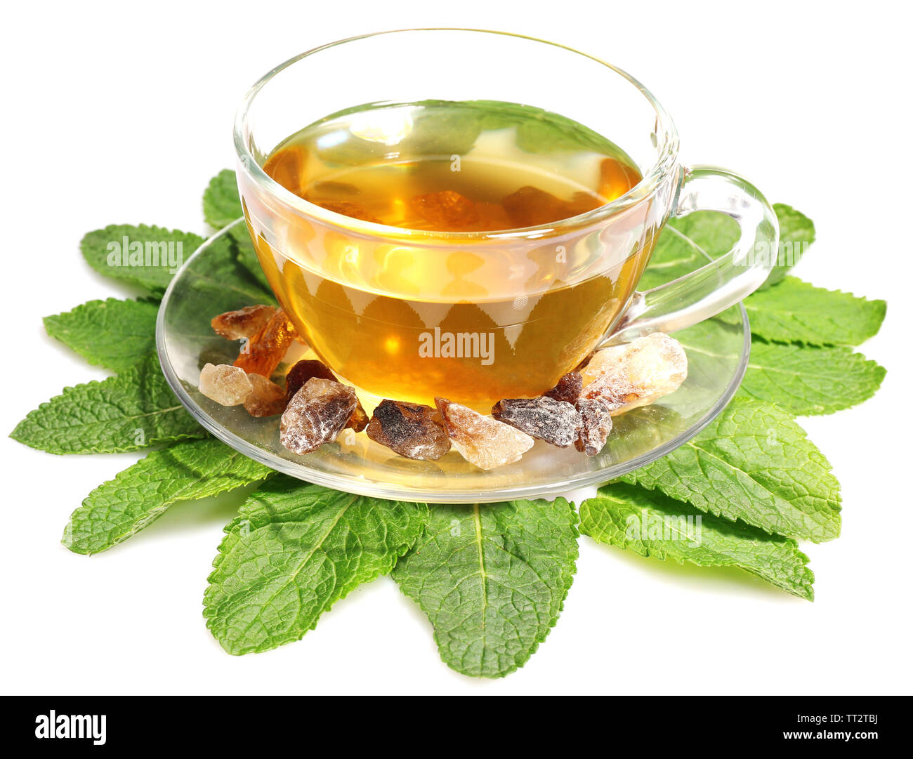 Composition of fresh mint leaves, mint tea in glass cup and brown sugar isolated on white - Stock Image