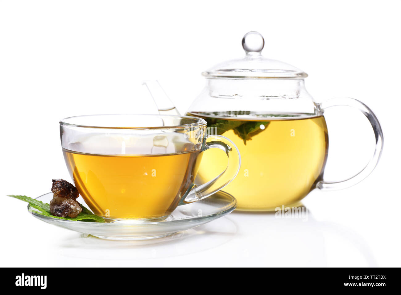 Composition of fresh mint tea in glass cup and teapot and brown sugar isolated on white - Stock Image
