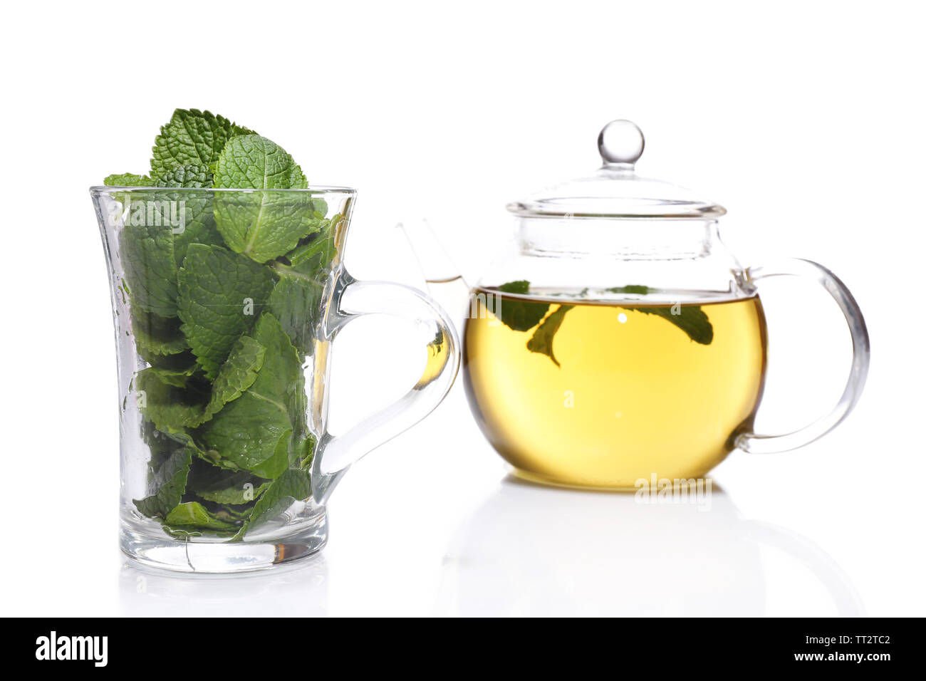 Composition of fresh mint leaves in glass cup and mint tea in teapot  isolated on white - Stock Image