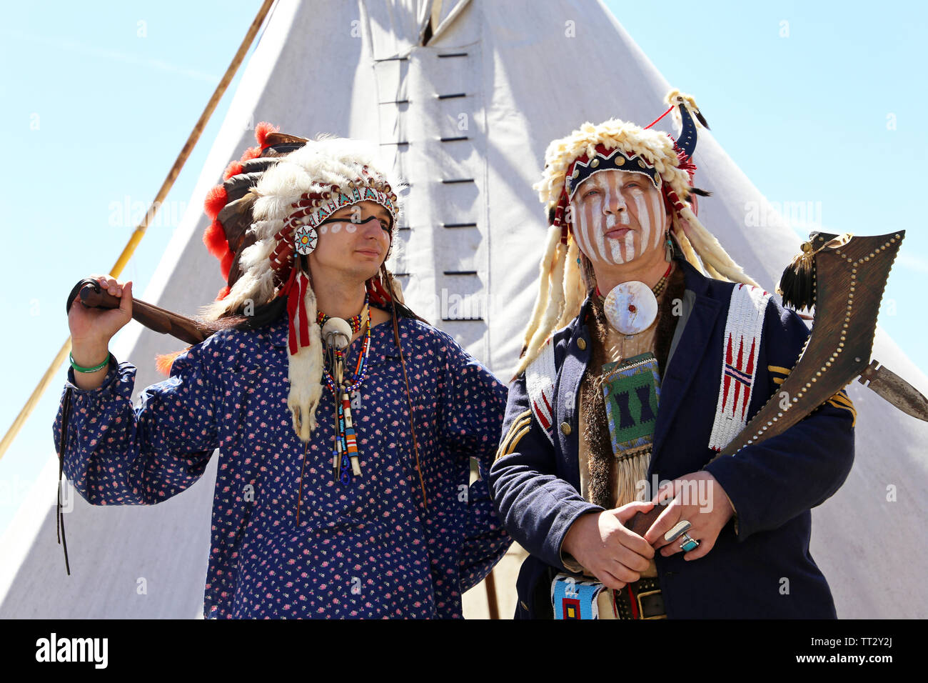 North American Indians stand with weapon near a wigwam against the blue sky. Reconstruction of native american life on Moscow historical festival - Stock Image