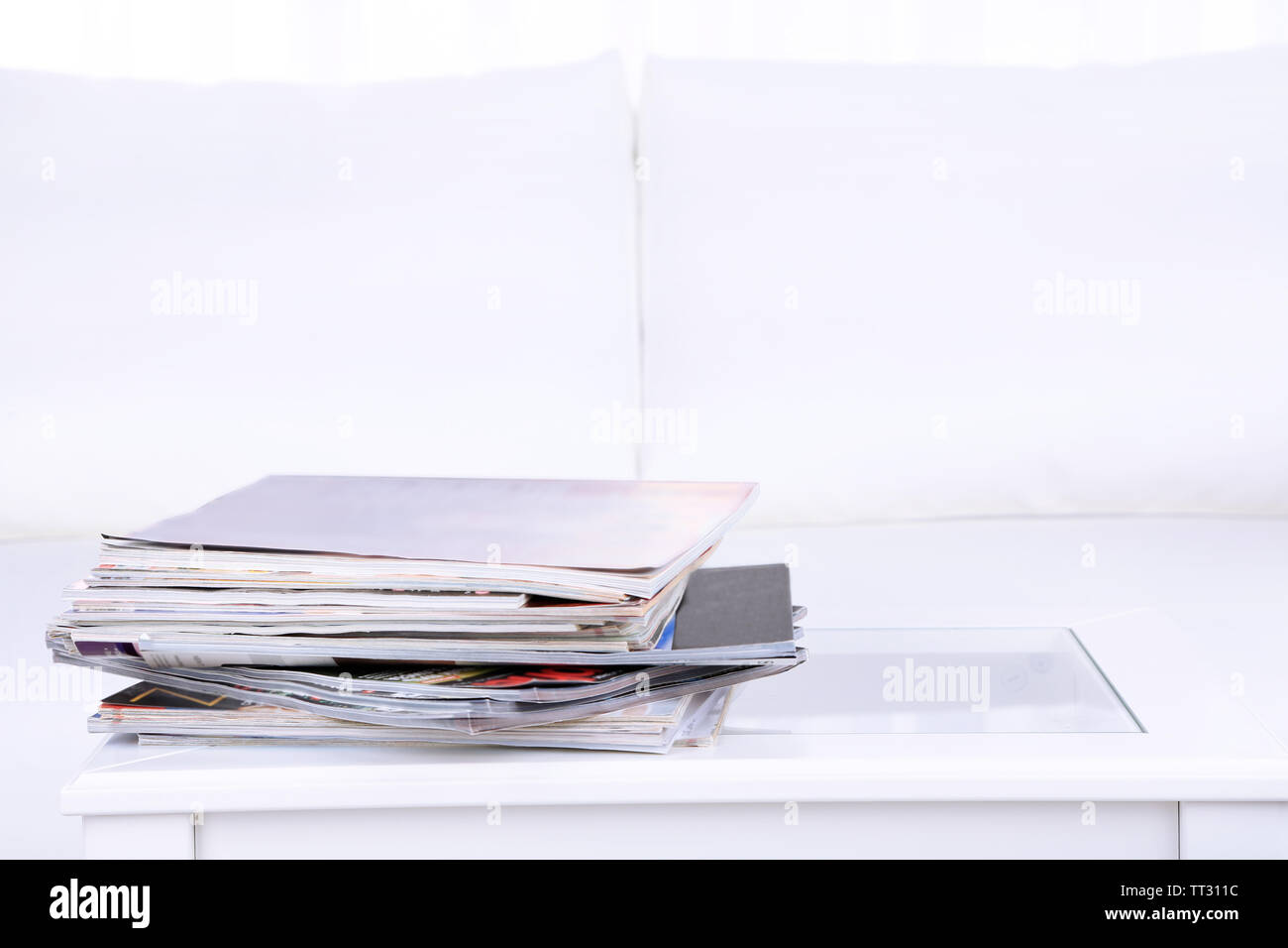 Magazines on coffee table in room - Stock Image