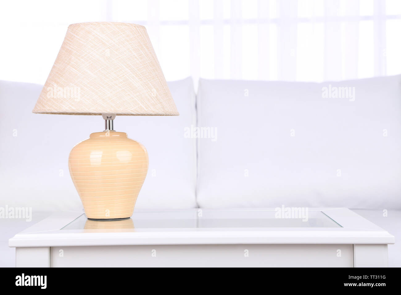 Lamp on coffee table in room - Stock Image