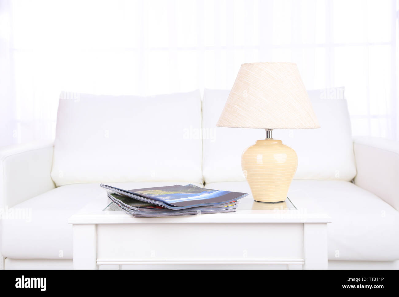 Magazines and lamp on coffee table in room - Stock Image
