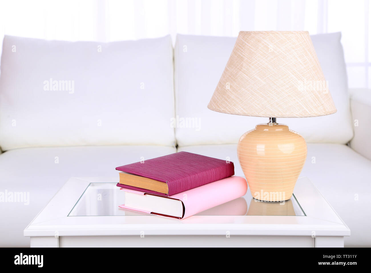 Books and lamp on coffee table in room - Stock Image