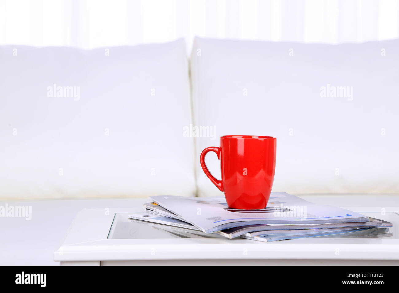 Magazines and cup on coffee table in room - Stock Image