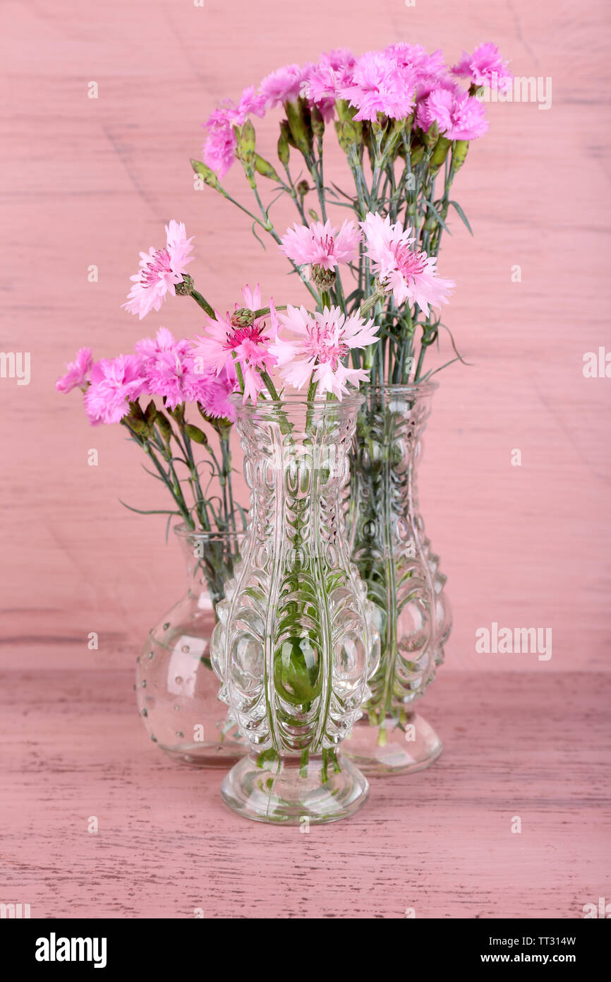 Alamy & Beautiful summer flowers in vases on pink wooden background ...