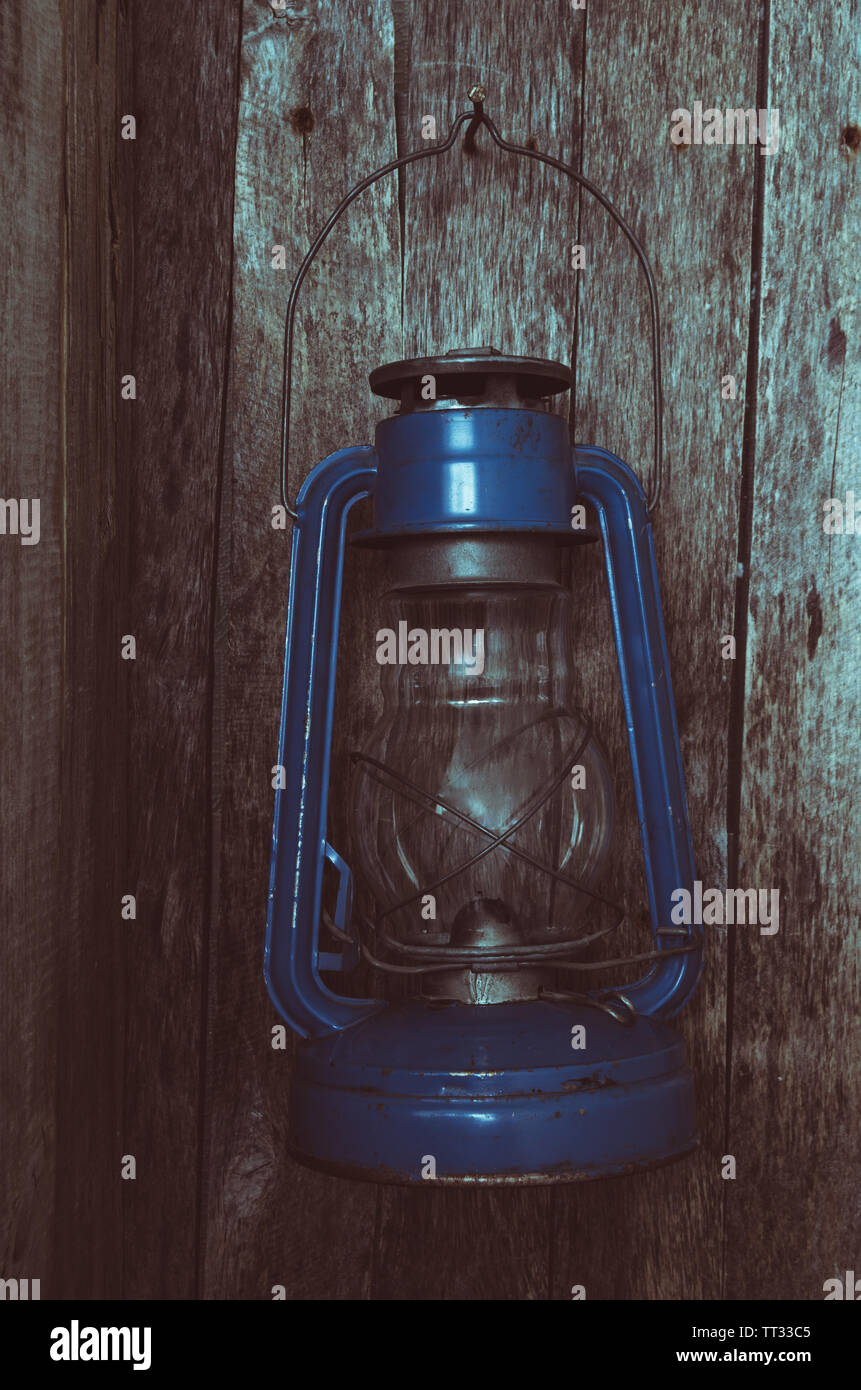 Extinguished the kerosene lamp hangs on old wooden wall in the morning - Stock Image