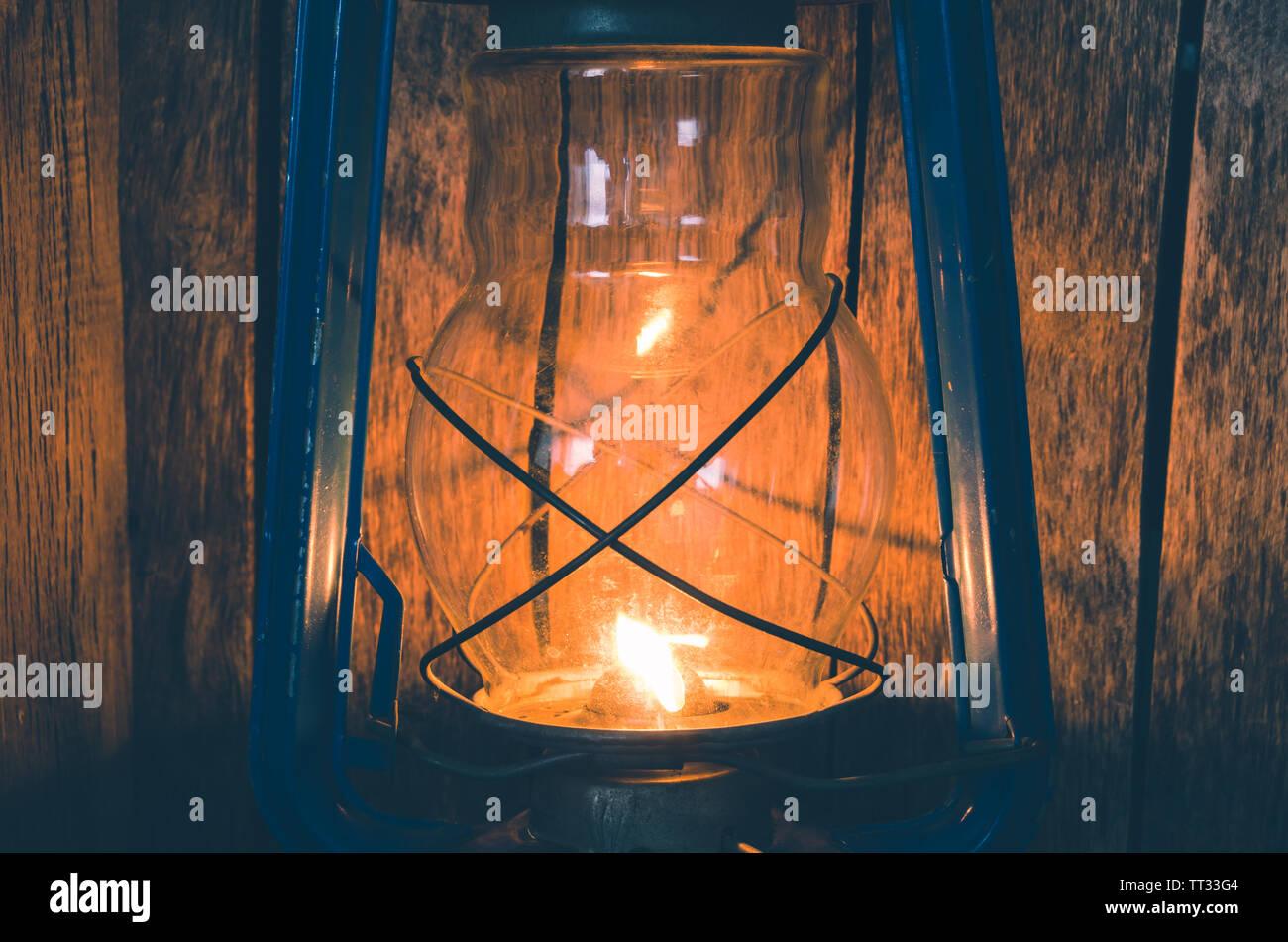 Old kerosene lamp illuminates the old wooden wall - Stock Image