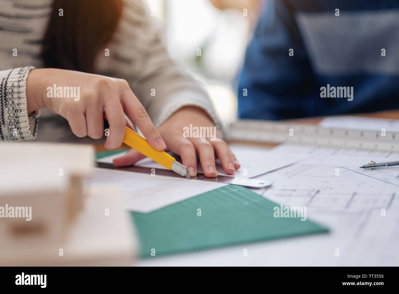 An architect working and cutting papers in office - Stock Image