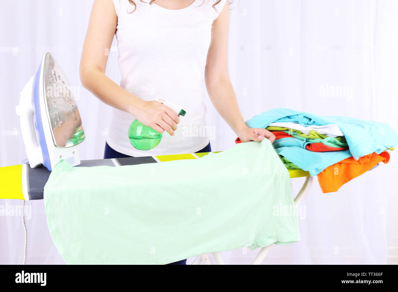 Woman ironing clothes on ironing board, close-up, on light background - Stock Image