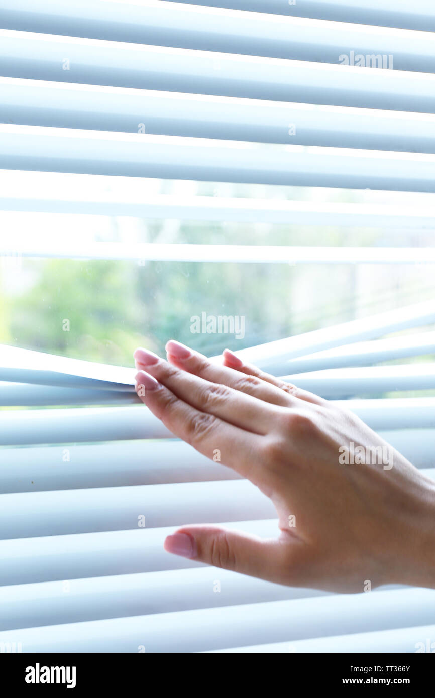 Female hand separating slats of venetian blinds with a finger to see through - Stock Image