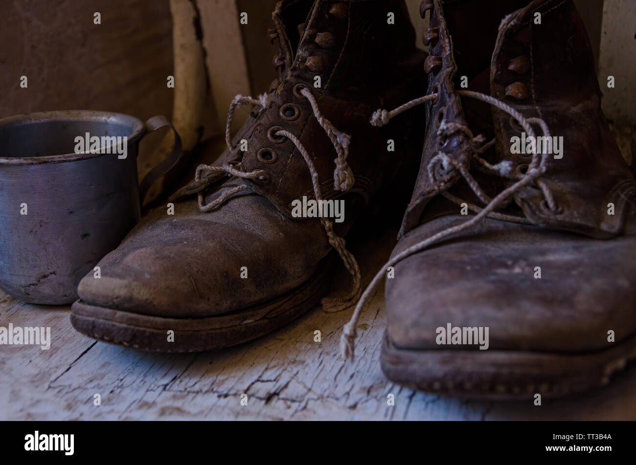 vintage old worn out work boots and a cup Stock Photo