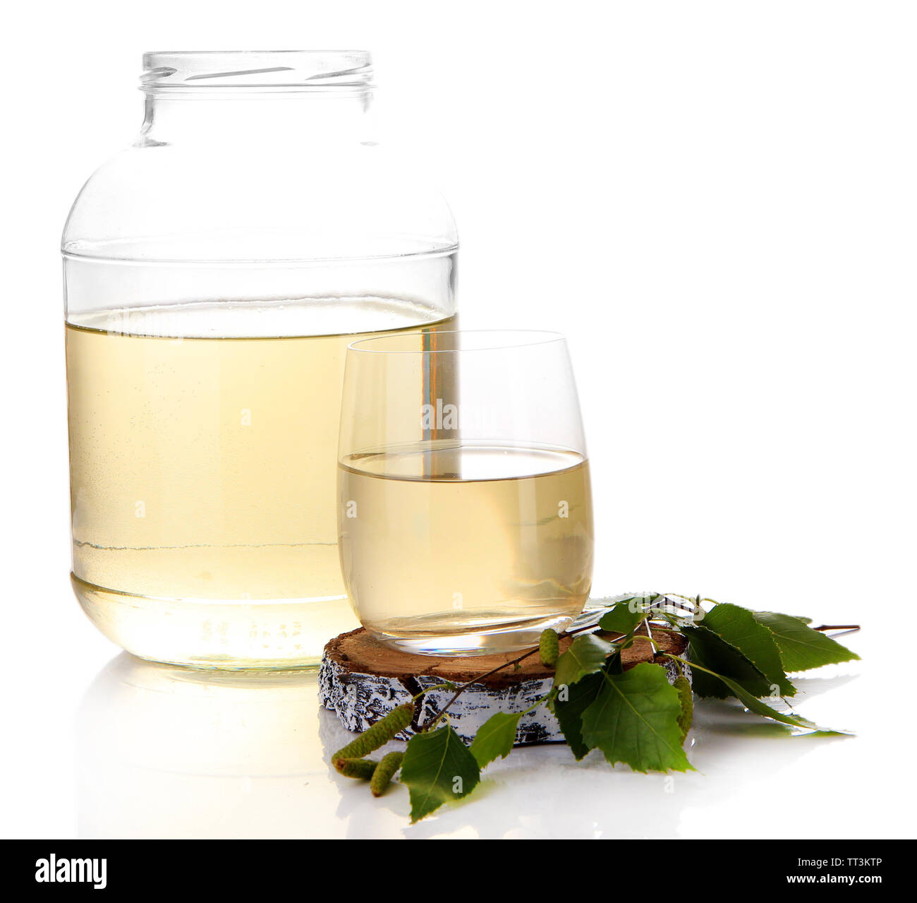 Glass and large flagon of fresh birch sap isolated on white Stock Photo