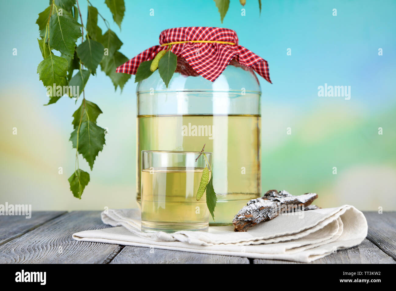 Glass and large flagon of fresh birch sap  on a wooden table on nature background Stock Photo