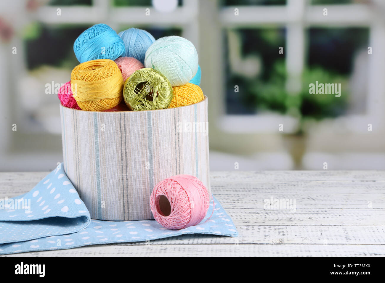 Clews of thread for hook knitting in box on the white table on window background - Stock Image