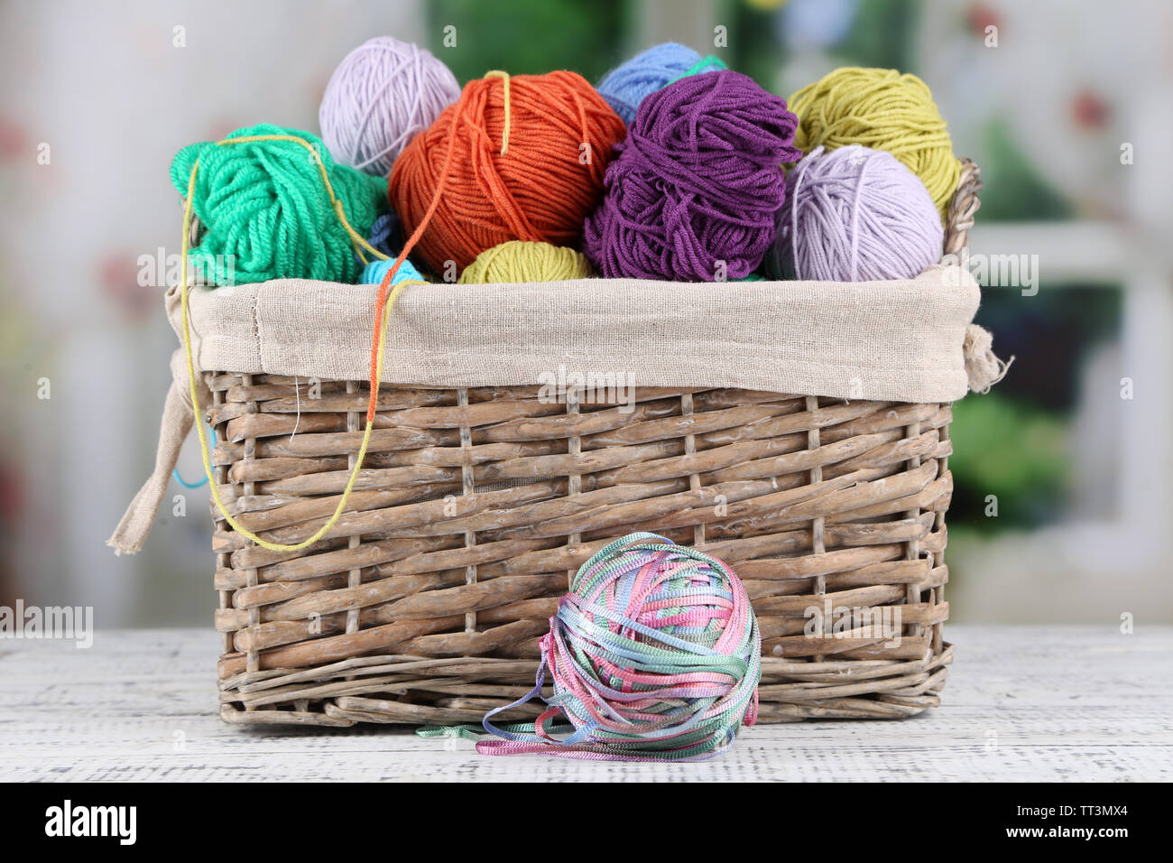 Multicoloured knitting yarn on a wooden table on window background - Stock Image