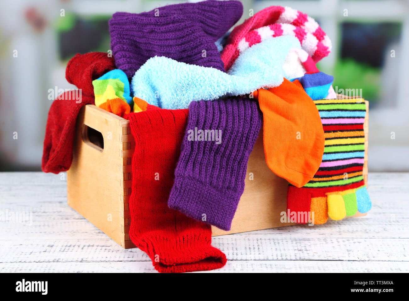 Multicoloured socks in a box on a wooden table in front of the window - Stock Image