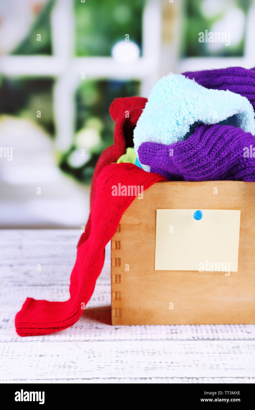 Multicoloured socks in box on a wooden table in front of the window - Stock Image